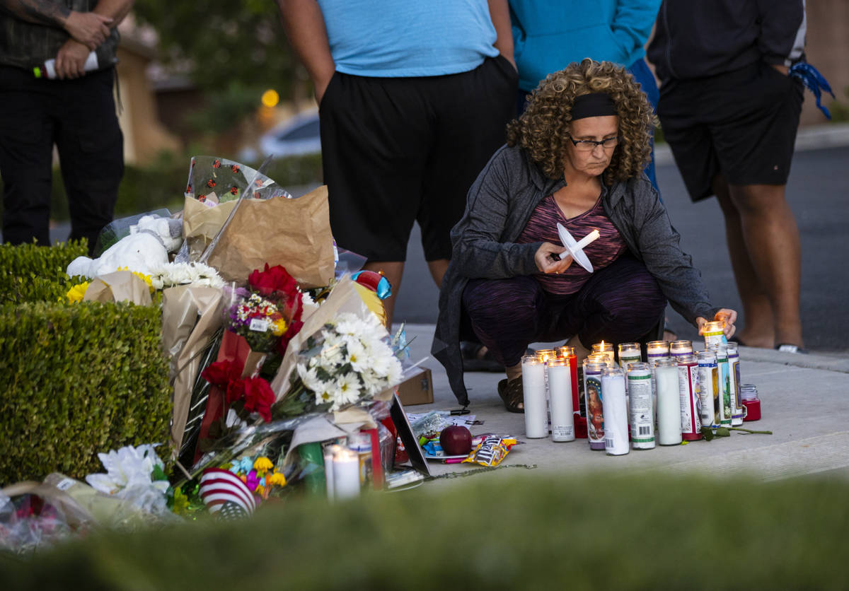 Marianne Littledike lights candles as people gather for a vigil in memory of David Cox, 18, and ...