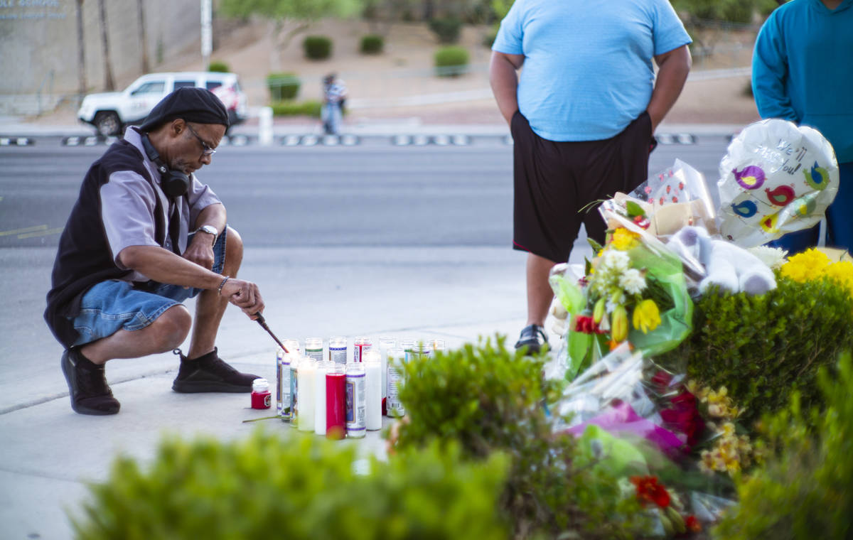 Mel E. lights candles as people gather for a vigil in memory of David Cox, 18, and Brandon Cox, ...