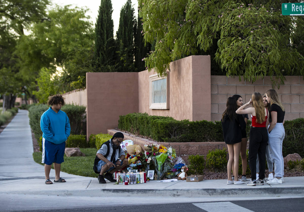 Mel E., second from left, lights candles as people gather for a vigil in memory of David Cox, 1 ...