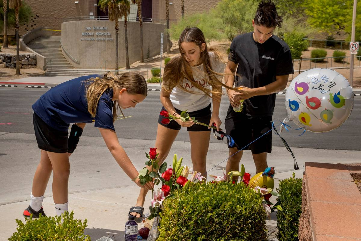 Former classmates stop by to leave roses at a small memorial near where two teen brothers were ...