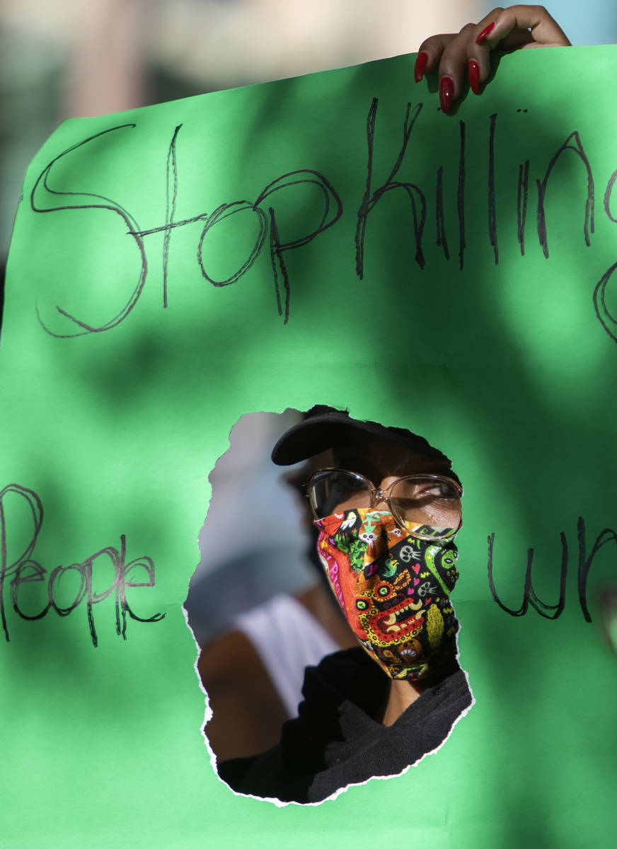 """One protester holds a sign reading """"Stop killing people who look like me"""" as the prot ..."""