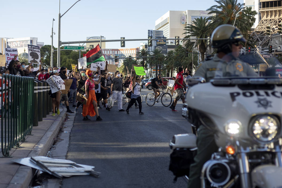 Protesters, who are calling for the police to be defunded and denouncing police brutality, move ...