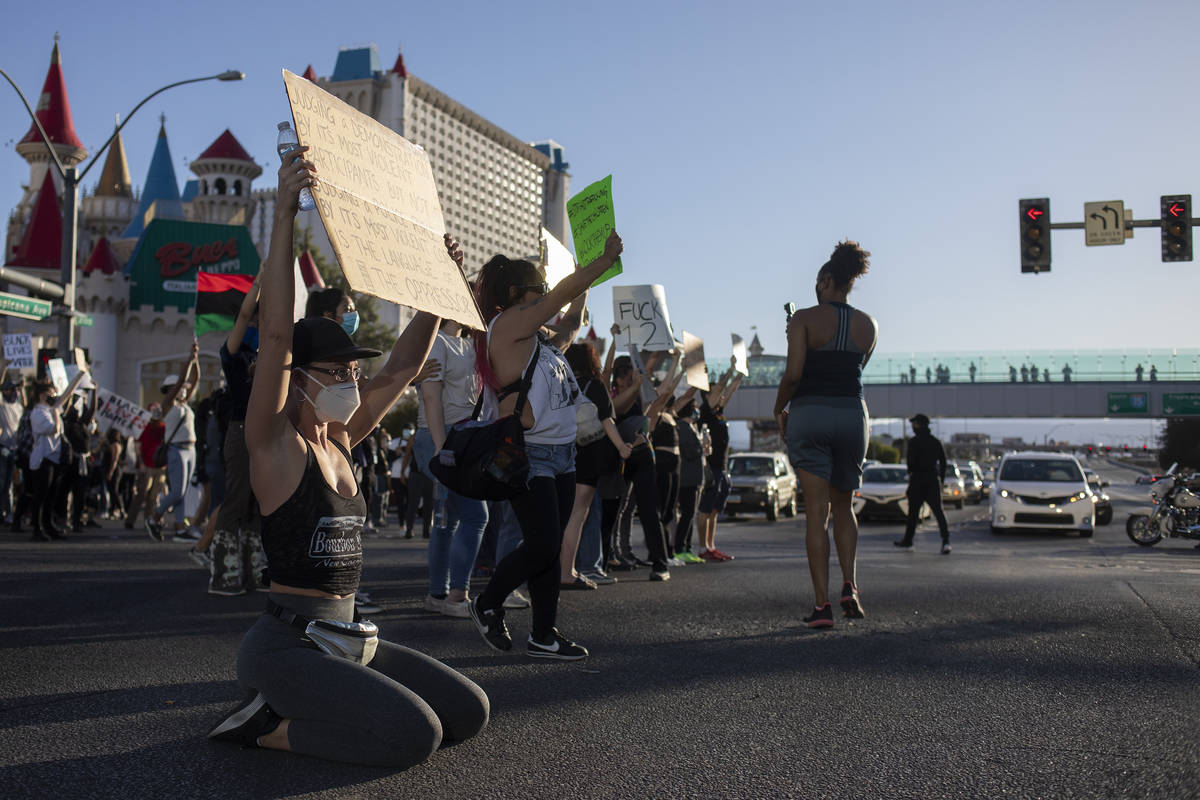 Protesters stop to show signs and chants to traffic at the intersection of Las Vegas Boulevard ...
