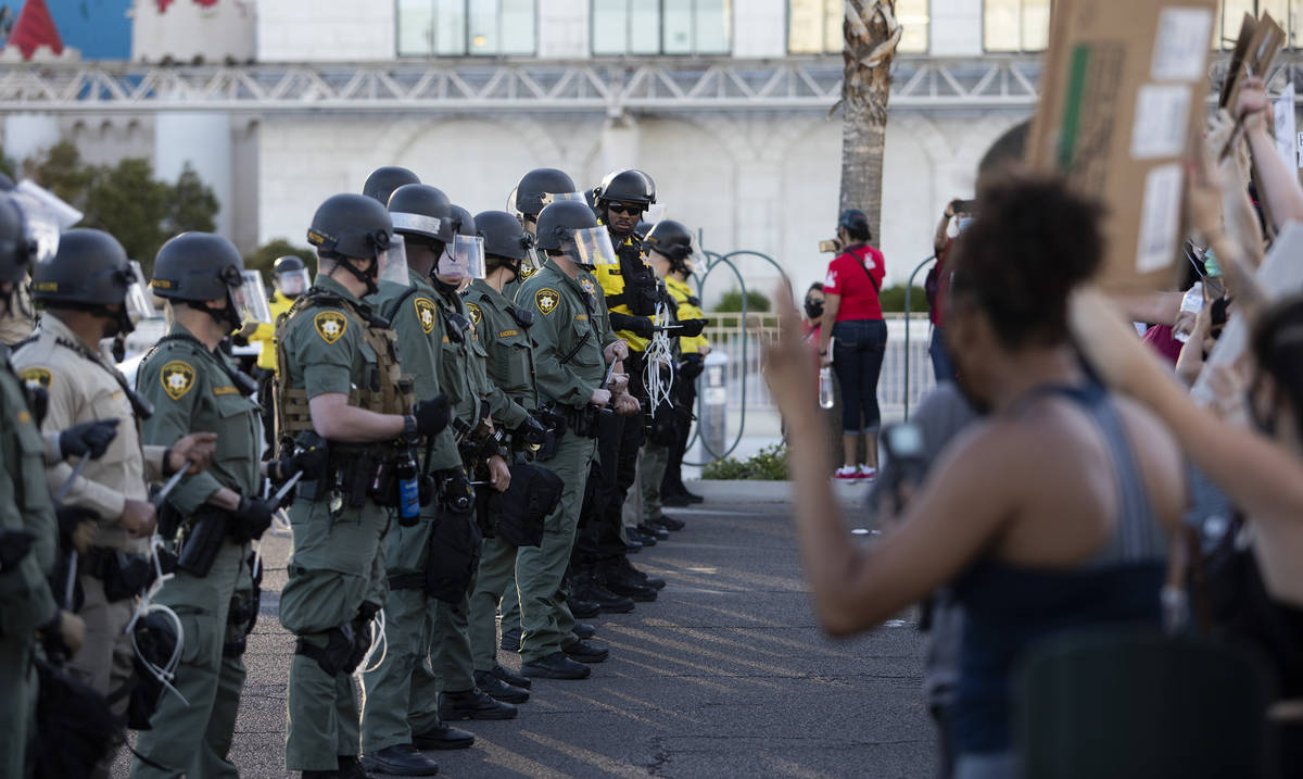 Police in riot gear and form a line outside Excalibur as protesters make way down Las Vegas Bou ...