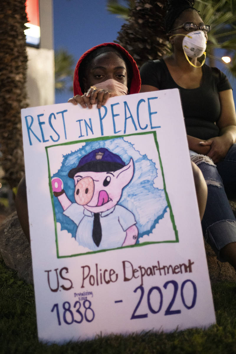 While waiting for a ride following a protest against police brutality, Avi Fielder holds up a s ...