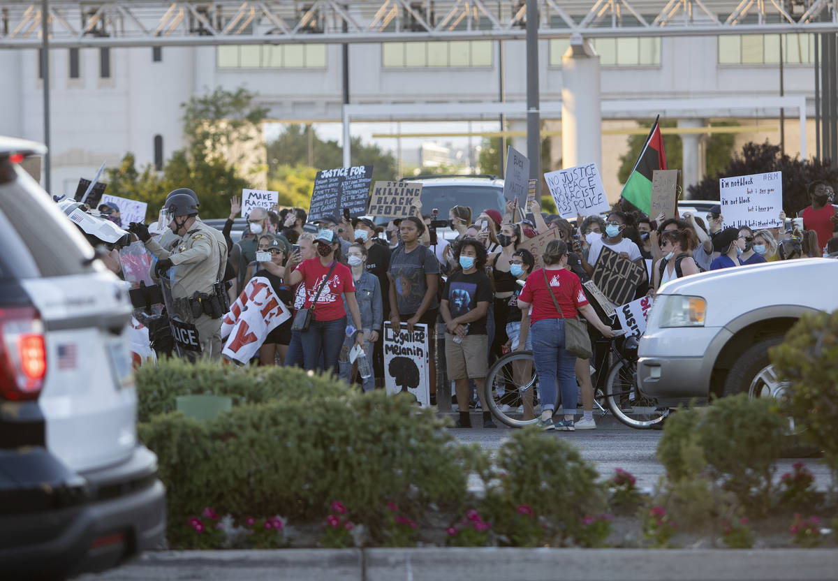 Legal observers stand in front of protesters as they make their way down Las Vegas Boulevard, m ...