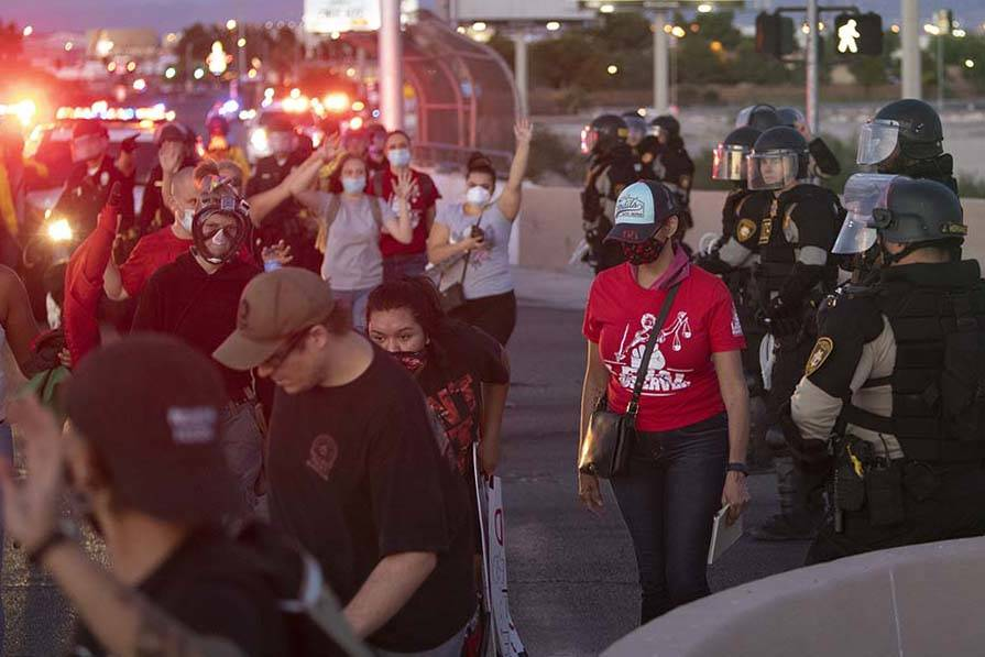Protesters pass police at an intersection with their hands up on Saturday, June 13, 2020 in Las ...