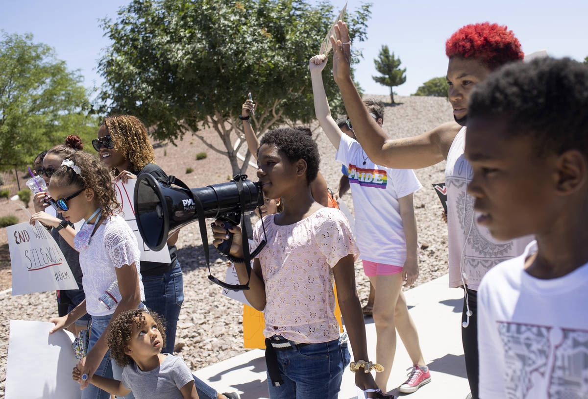 """Chasadity Patterson-Hudson, center, 11, takes a turn on the megaphone to chant """"no justice ..."""