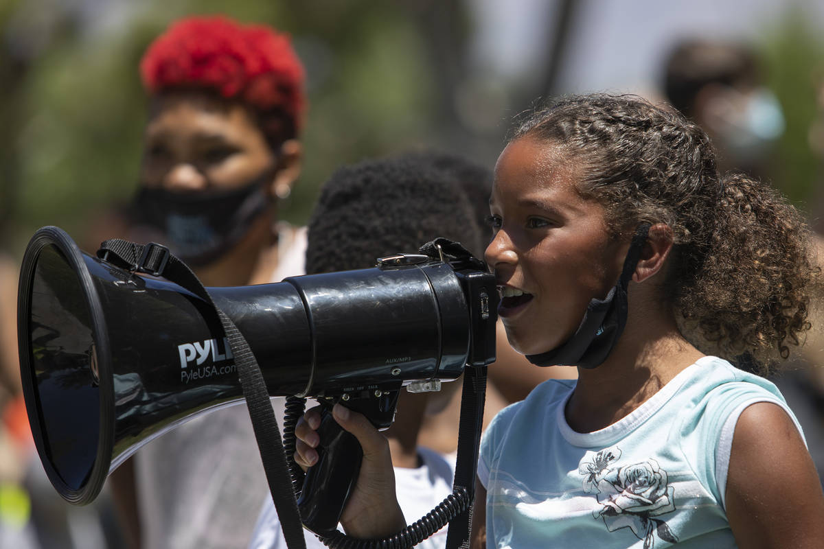 """Paige Faggins, 9, takes a turn to chant into the megaphone at the """"Kids Against Racism Ral ..."""