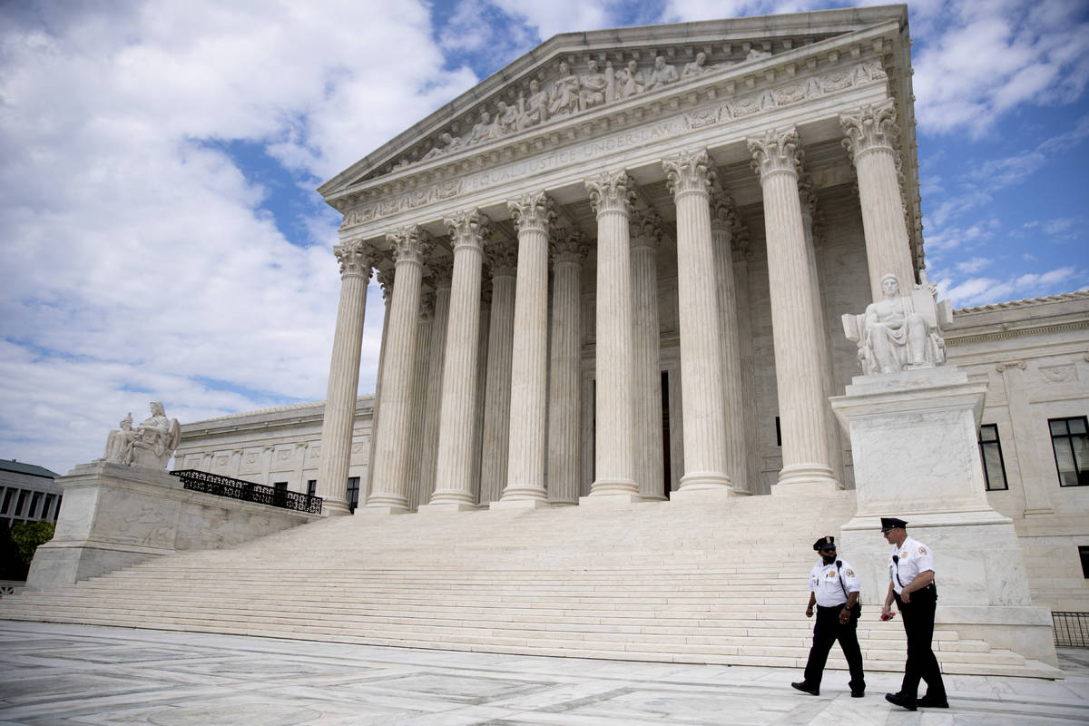 FILE - In this May 14, 2020, file photo security officers walk in front of the Supreme Court in ...