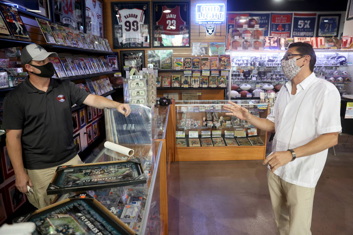 Jeremy Brown, owner of Ultimate Sports Cards and Memorabilia, talks to David Martinez of Delton ...