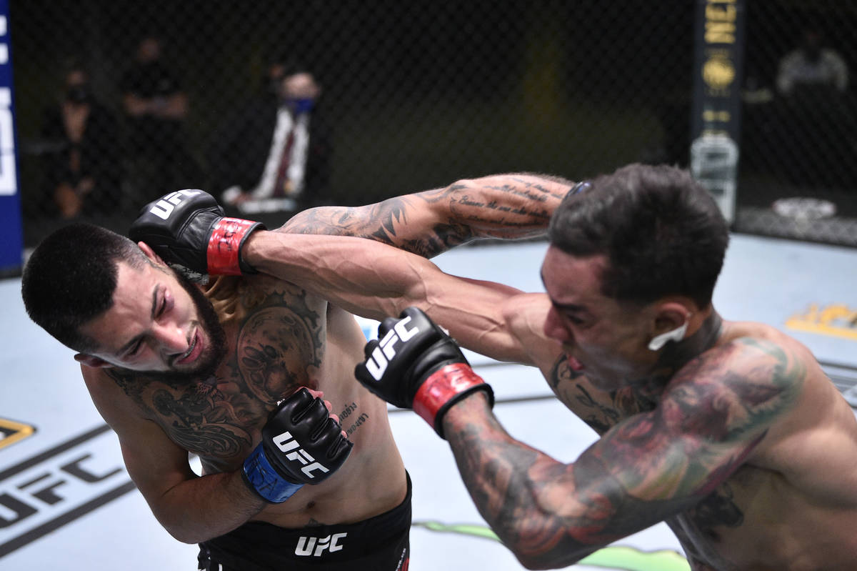 Charles Jourdain of Canada and Andre Fili trade punches in their featherweight fight during the ...