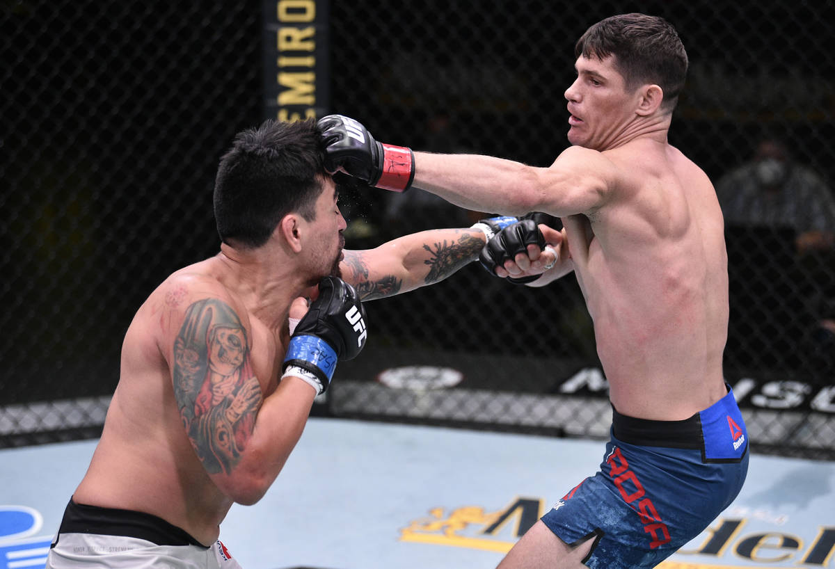 Charles Rosa punches Kevin Aguilar in their lightweight fight during the UFC Fight Night event ...