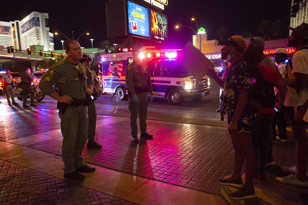A protester argues with a Las Vegas Metropolitan Police officer as an ambulance arrives to take ...