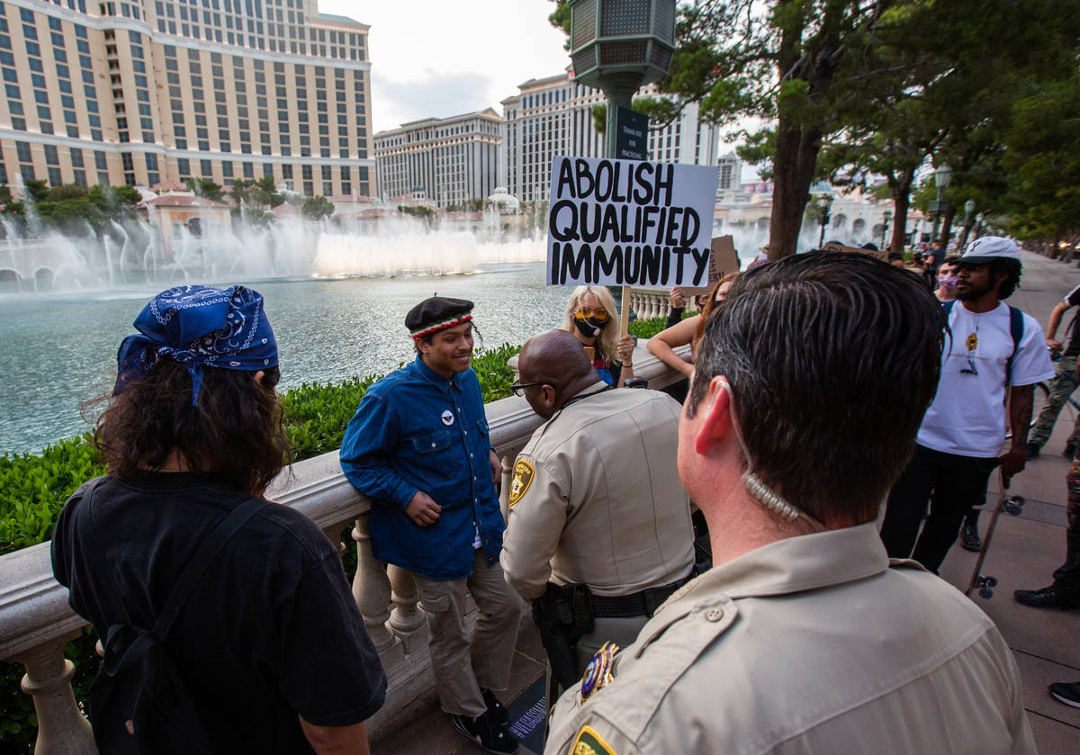 Porfirio Flores, a Black Lives Matter protester, speaks with Las Vegas police officers in front ...
