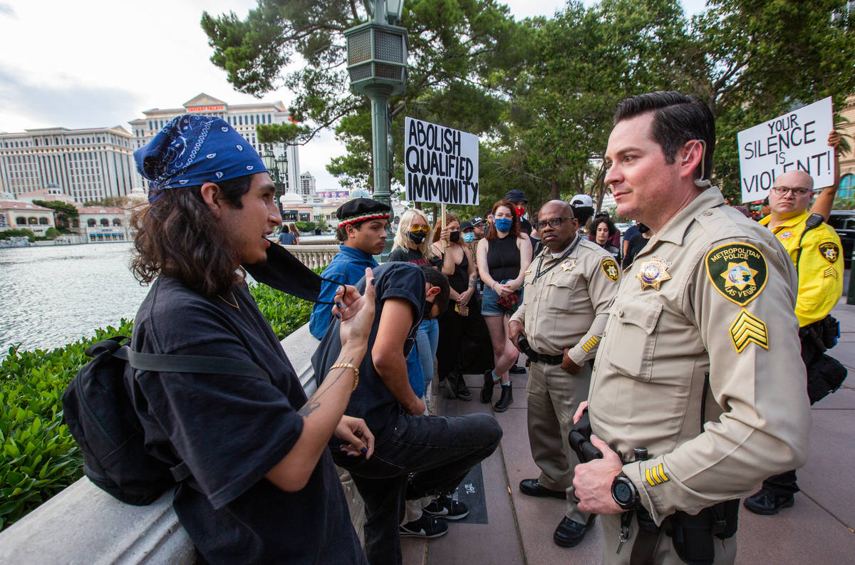 Black Lives Matter protesters speak with Las Vegas police officers in front of the Bellagio fou ...