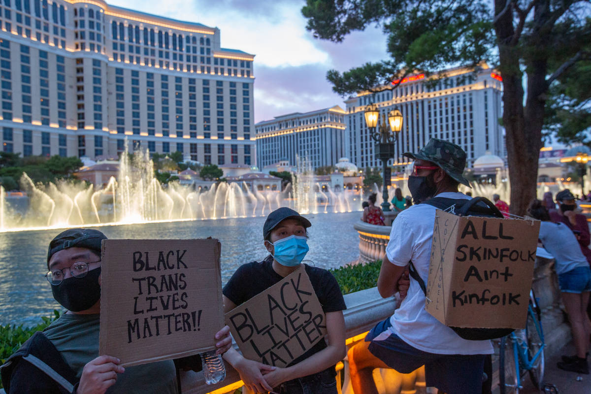 Black Lives Matter protesters hold signs in front of the Bellagio fountains in Las Vegas on Mon ...