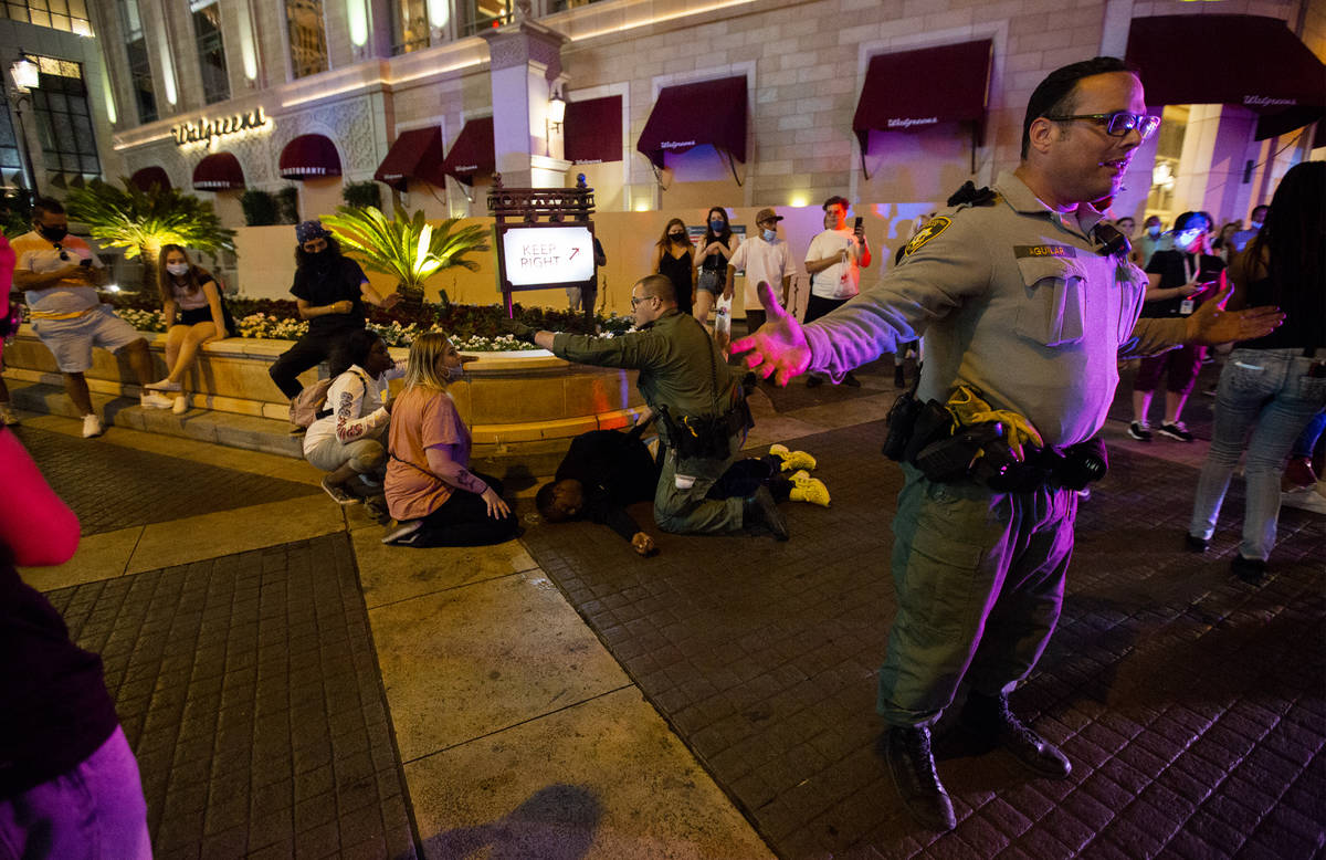 Las Vegas Metropolitan Police officers ask protesters to stand back as an officer kneels on a m ...