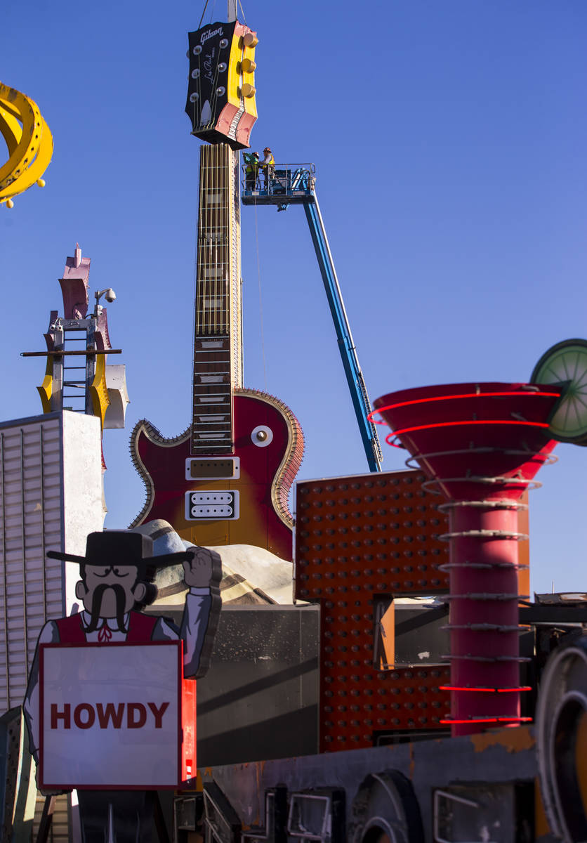 The headstock piece of the Hard Rock Cafe guitar sign is raised into the air as YESCO employees ...