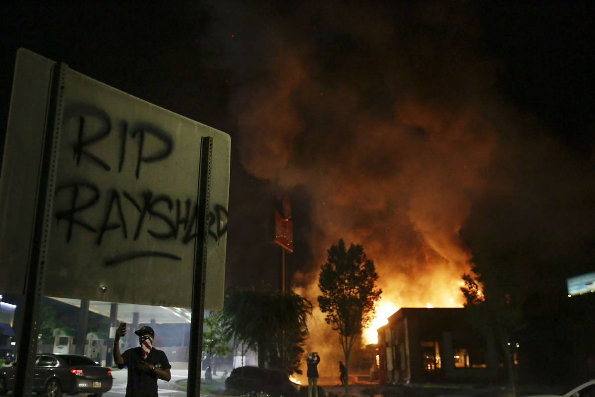 """""""RIP Rayshard"""" is spray painted on a sign as as flames engulf a Wendy's restaurant du ..."""
