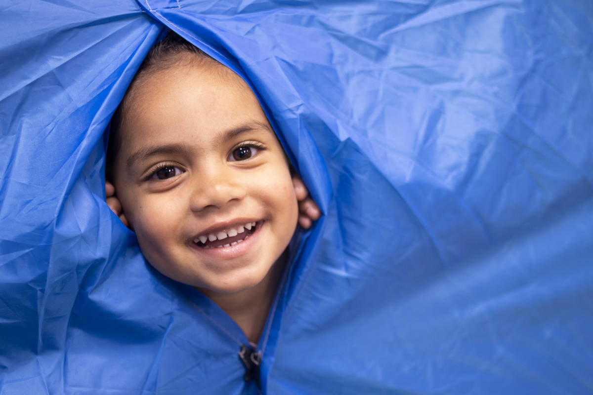 """Paisley peeks through the tent, which is in one of the preschool rooms for """"camping week,& ..."""