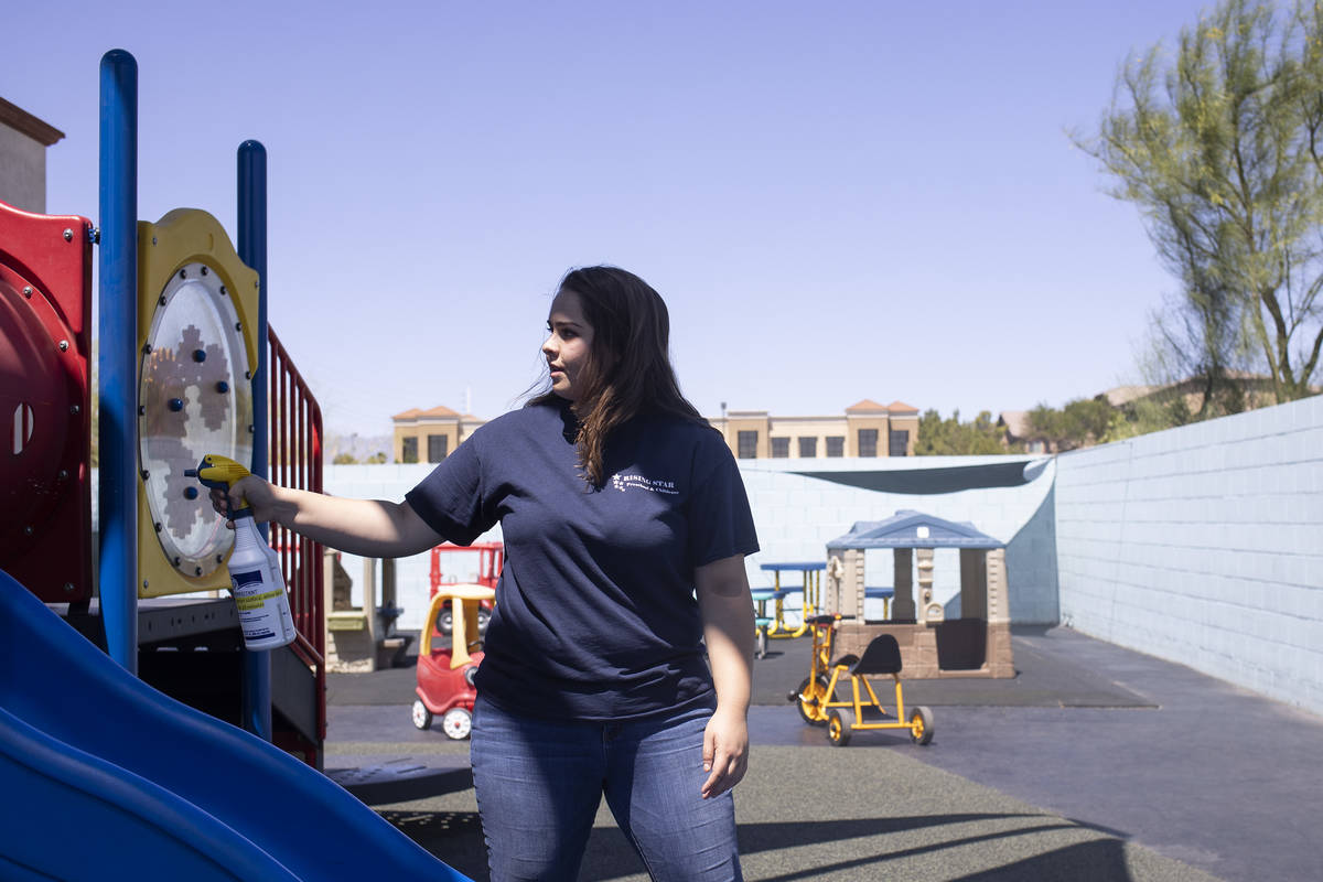 Miss Destaney sprays the playground with disinfectant after her class had outside time at Risin ...