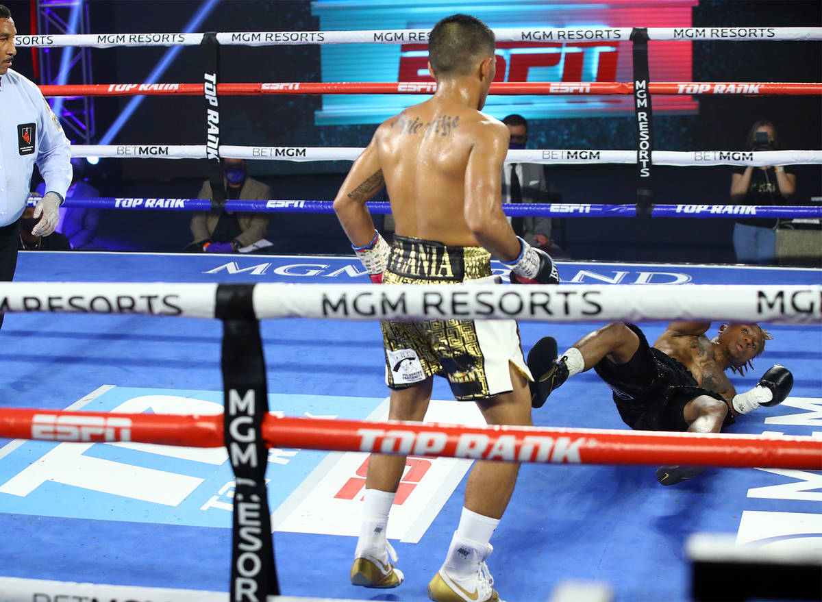 Mike Plania knocks down Joshua Greer Jr. during their bantamweight fight inside the MGM Grand's ...