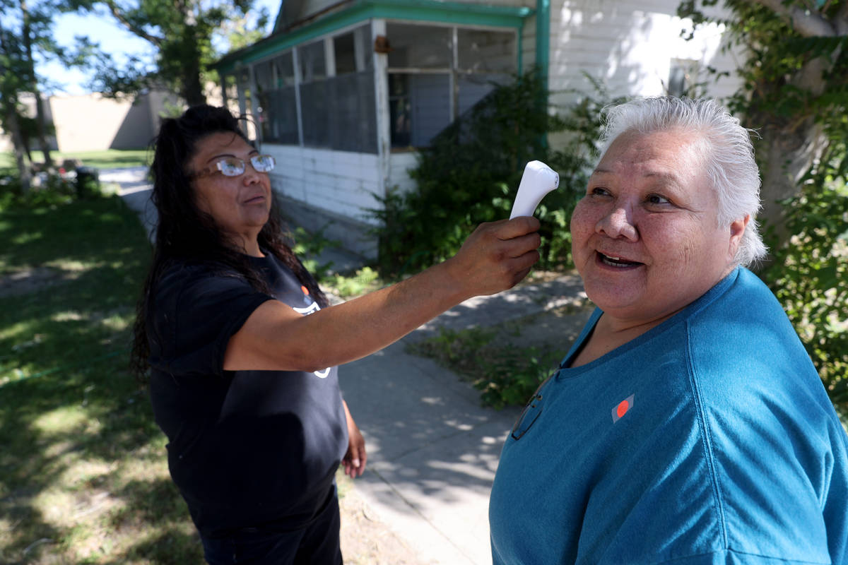 Deanna Garcia, left, checks the temperature of an unidentified member at Walker River Paiute Tr ...
