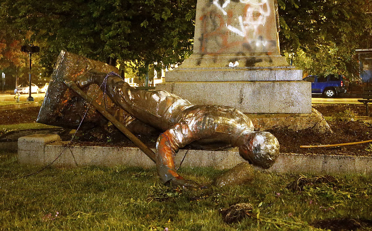 A statue from the Richmond Howitzers Monument in Richmond, Va., lies after being toppled Tuesda ...