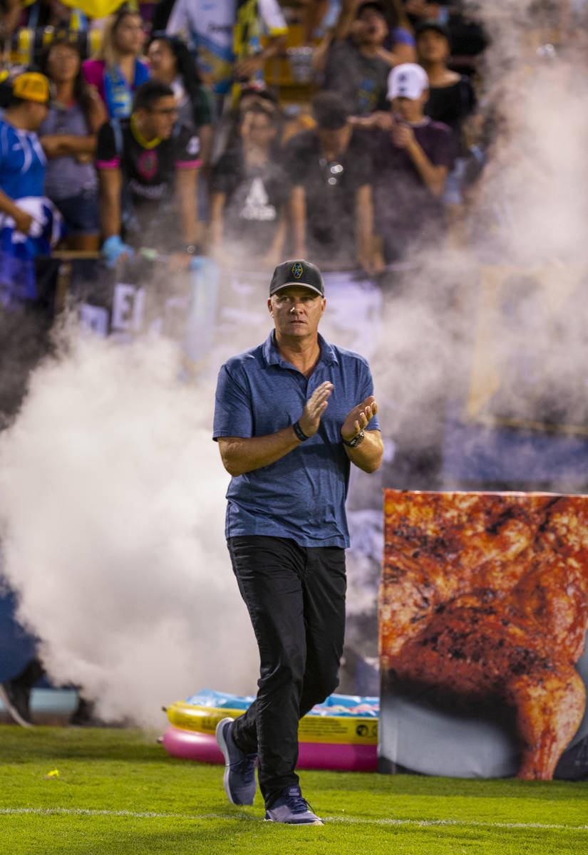 Las Vegas Lights FC head coach Eric Wynalda emerges from the smoke onto the field to face the P ...