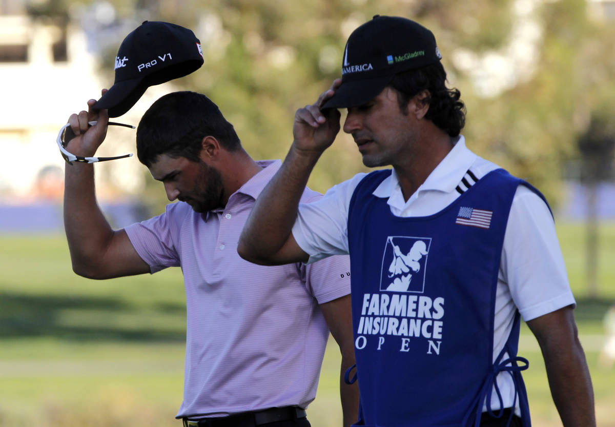 Kyle Stanley, left, and his caddie Brett Waldman walk off the 16th green where Stanley lost a p ...