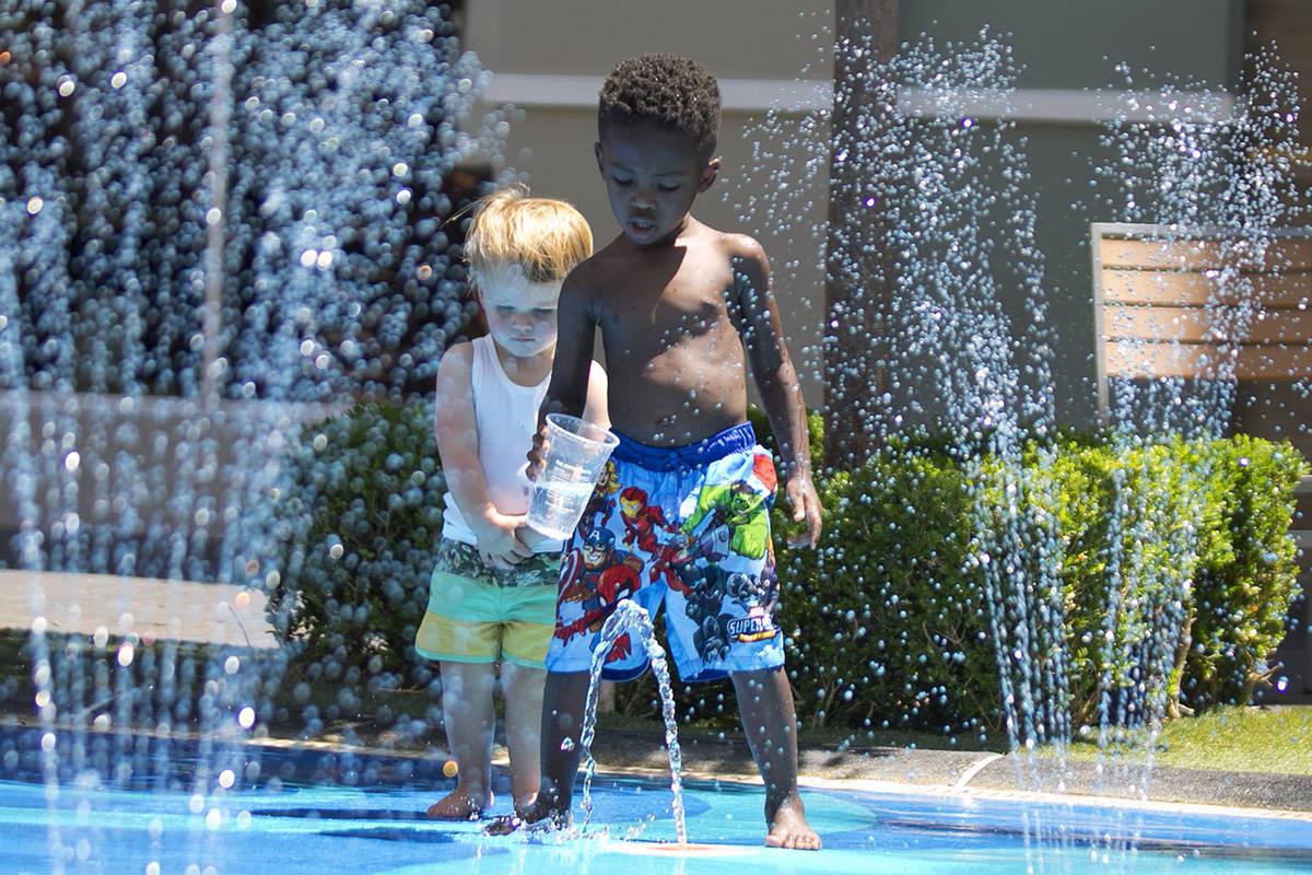 Mason Lanni, 2, left, and Mason, who declined to give his last name, play at a splash pad at Th ...