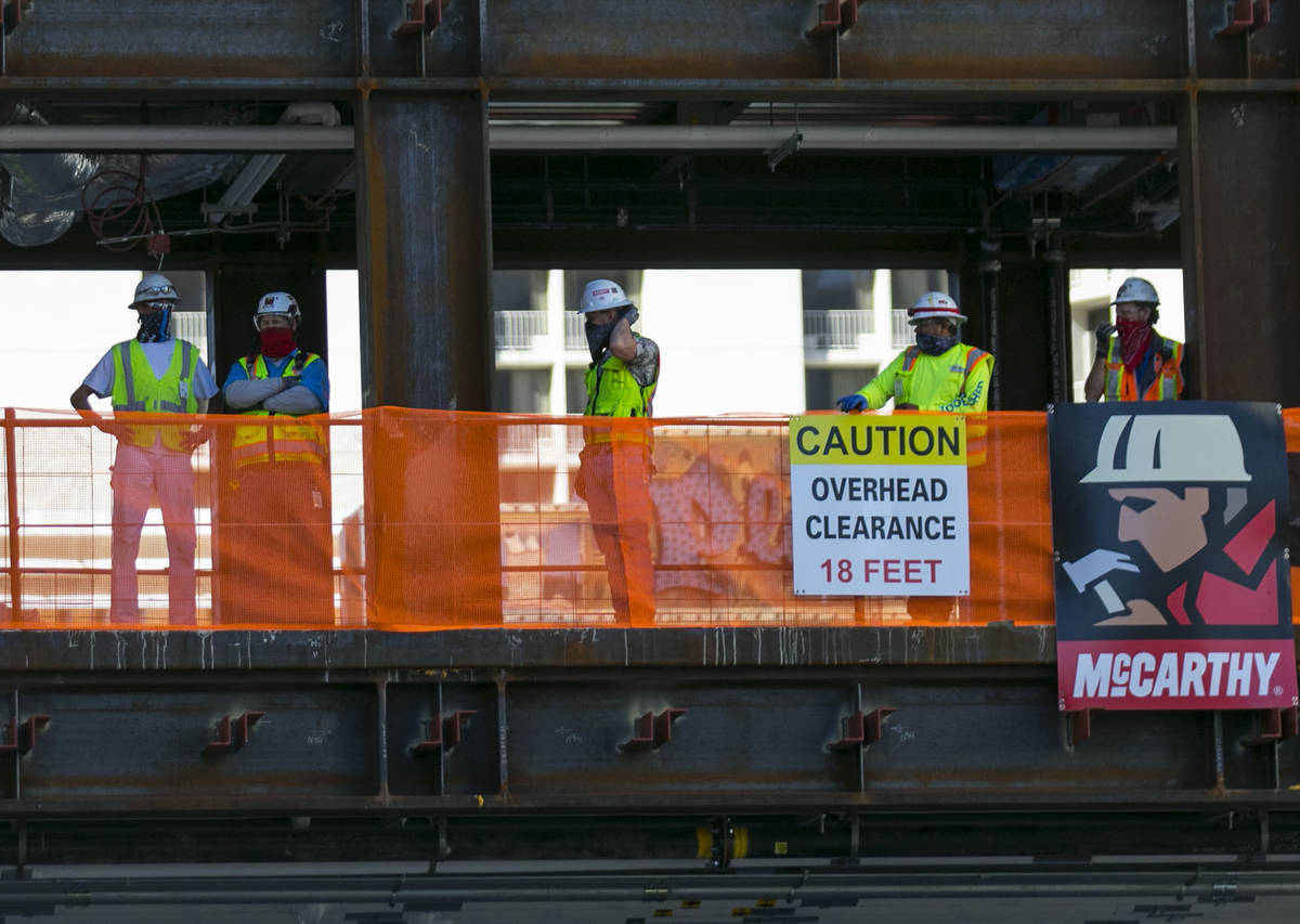 Workers watch as the last steel beam, signed by Derek Stevens, CEO and developer of Circa Resor ...