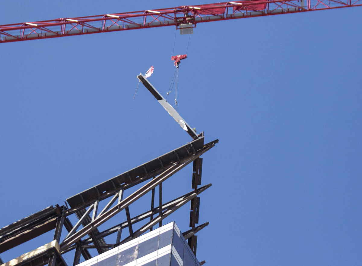 Workers hoist the last steel beam signed by Derek Stevens, CEO and developer of Circa Resort a ...
