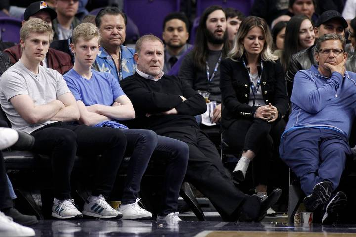 Phoenix Suns owner Robert Sarver, center, watches during the second half of an NBA basketball g ...