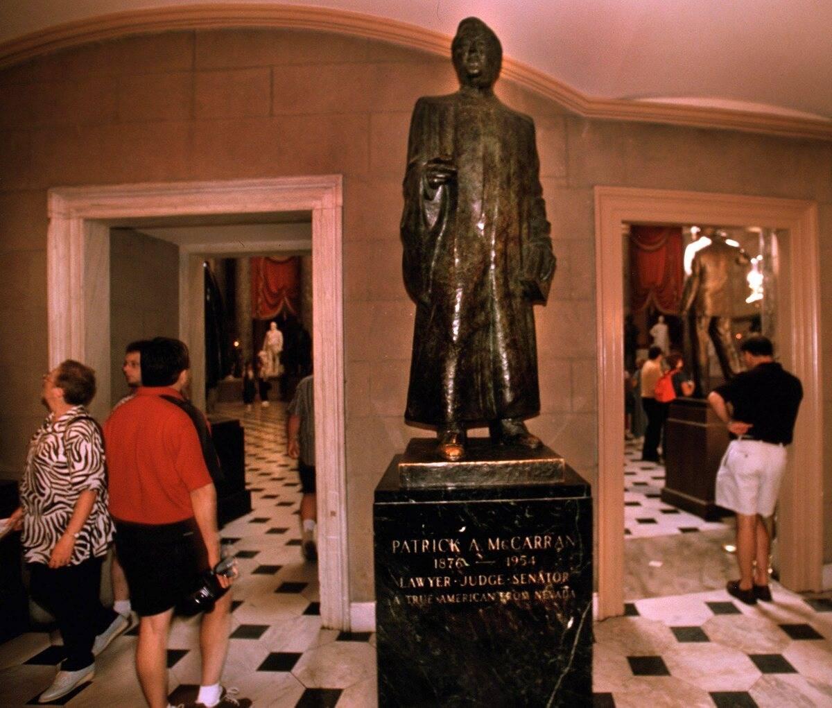 Tourist pass the statue of Nevada Senator Pat McCarran, located in the National Statuary Hall i ...