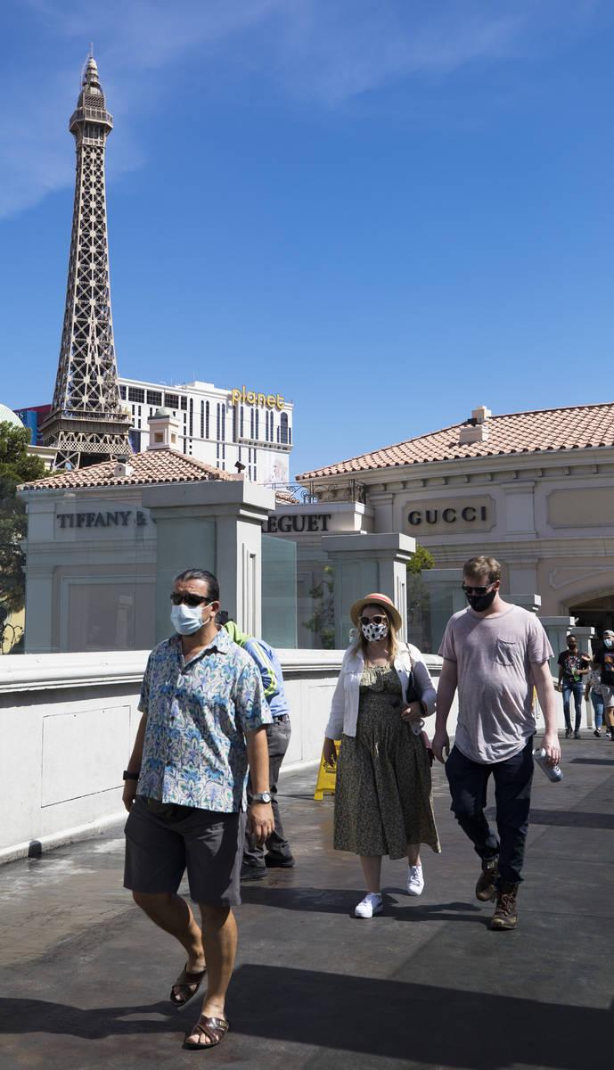 Visitors cross a pedestrian bridge on the Strip in Las Vegas, Sunday, June 21, 2020. (Rachel As ...