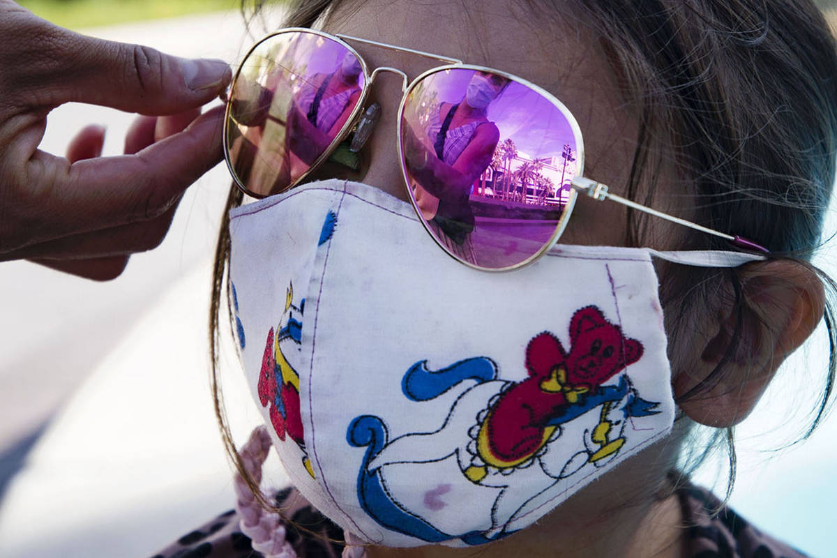 Jannete Gurrola, of Los Angeles, adjusts the sunglasses on her daughter Nadia Saucedo, 4, outsi ...