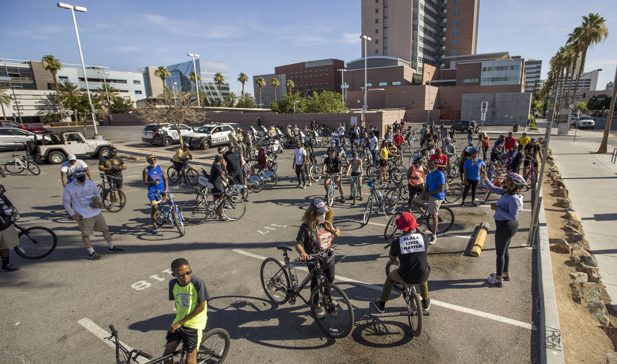Participants in a Black Lives Matter bike ride against injustice gather in a parking lot off of ...