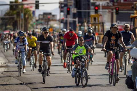 Participants in a Black Lives Matter bike ride against injustice pass by the Resort's World con ...