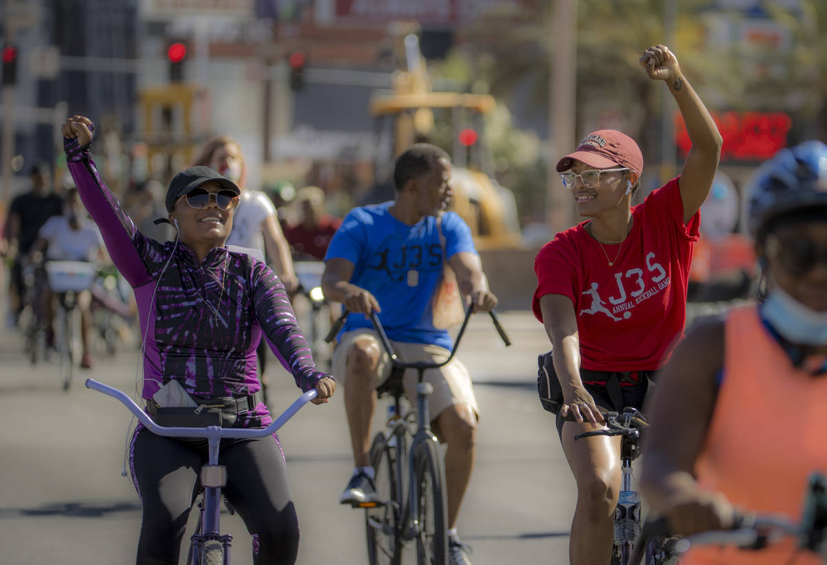 Participants in a Black Lives Matter bike ride against injustice show their support while passi ...