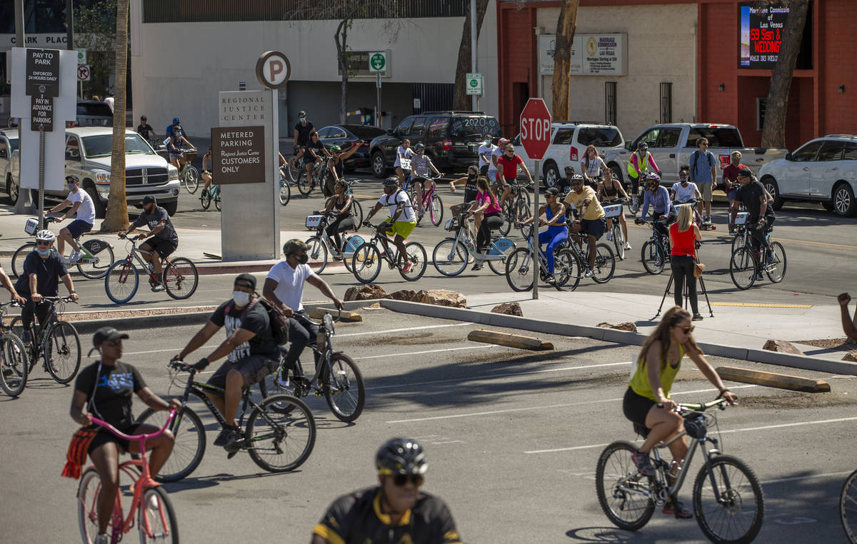 Participants in a Black Lives Matter bike ride against injustice return to a parking lot off of ...