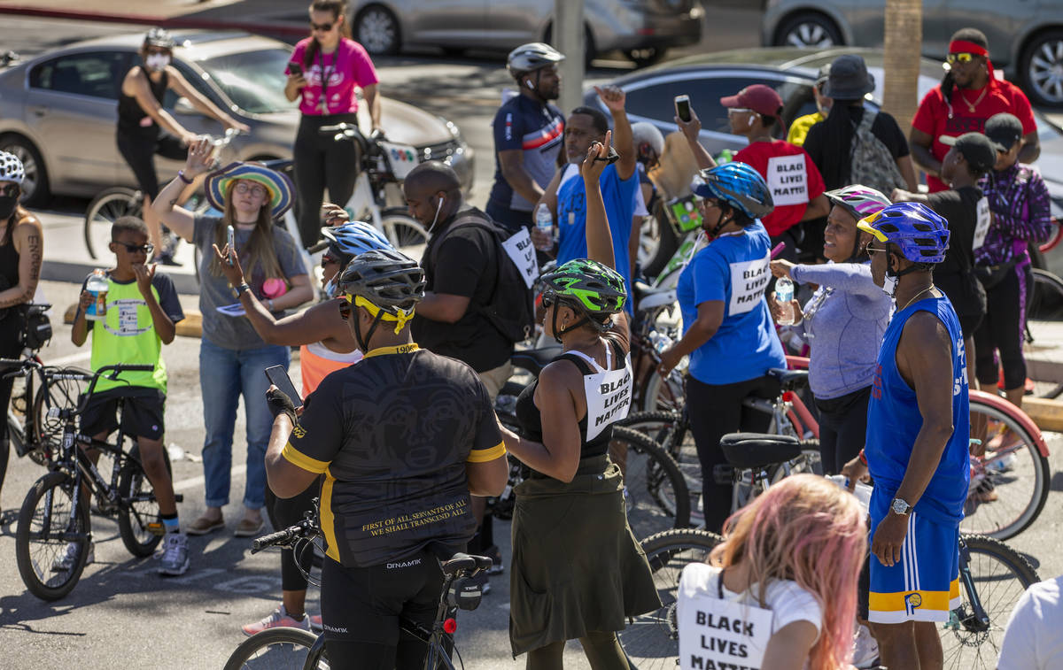 Participants in a Black Lives Matter bike ride against injustice cheer after returning to a par ...