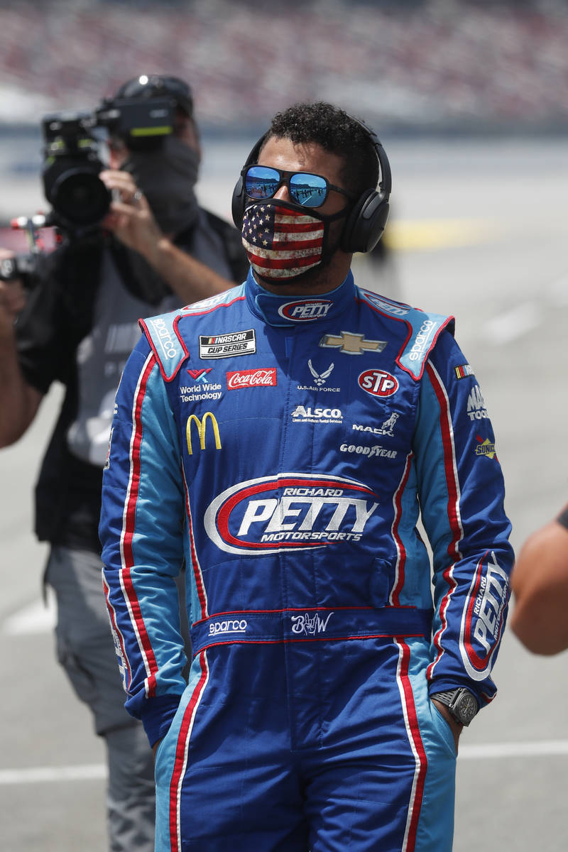 Driver Bubba Wallace walks to his car in the pits of the Talladega Superspeedway prior to the s ...
