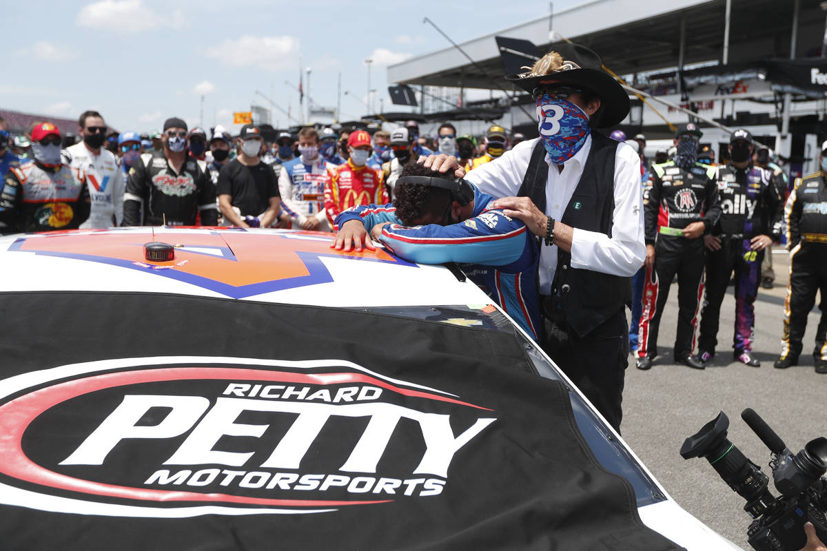 Driver Bubba Wallace, left, is overcome with emotion as team owner Richard Petty, comforts him ...
