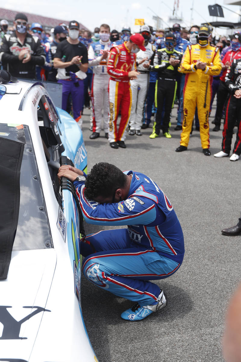 Driver Bubba Wallace, front, is overcome with emotion as he arrives at his car in the pits of t ...
