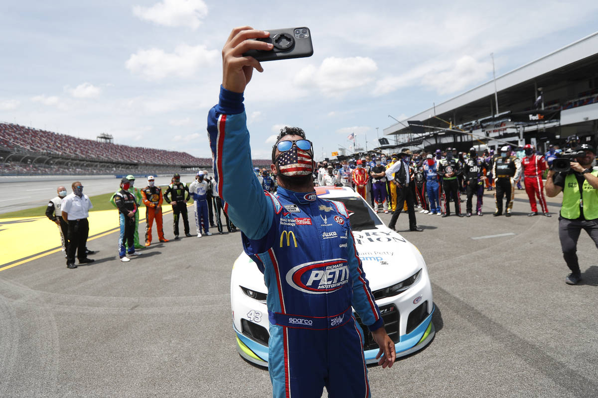Driver Bubba Wallace takes a selfie with himself and other drivers that pushed his car to the f ...