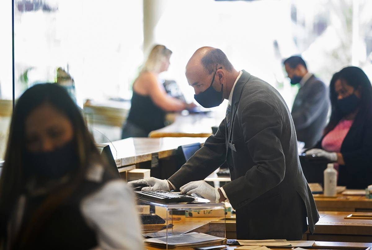 Guest service representatives wear protective masks and gloves while checking people in at TI o ...