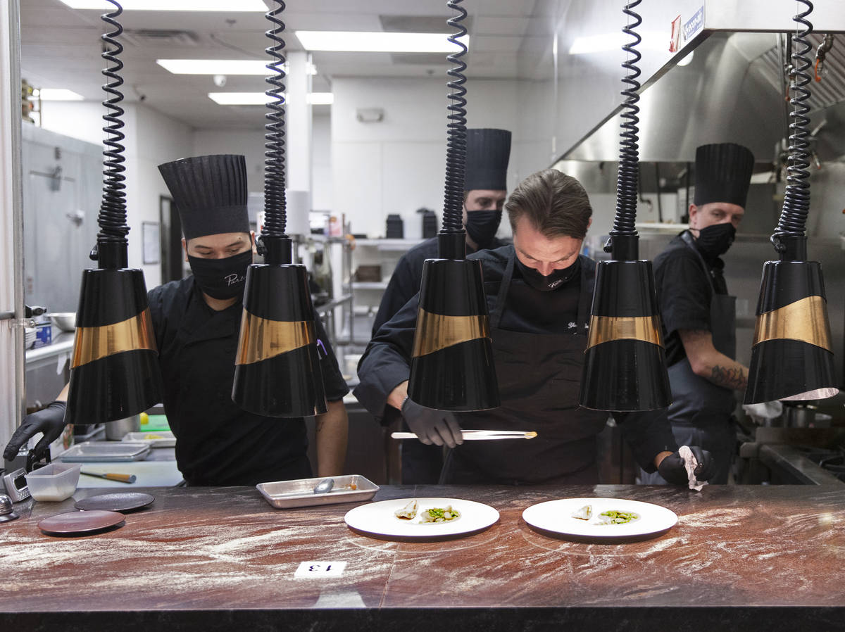 Chef Yuri Szarzewski, top/right, wears a protective mask while preparing food in the kitchen at ...