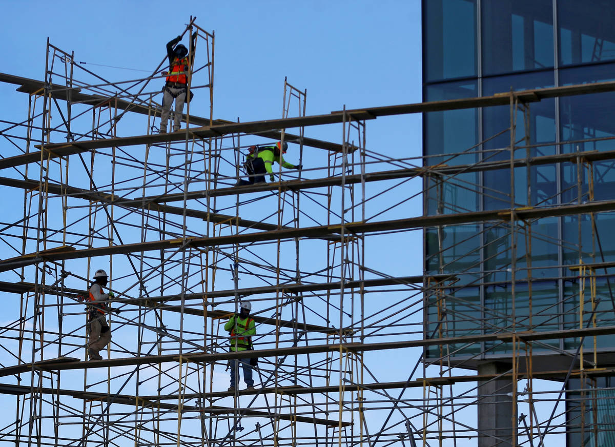 Workers remove scaffolding on the west side of the Las Vegas Convention Center expansion projec ...